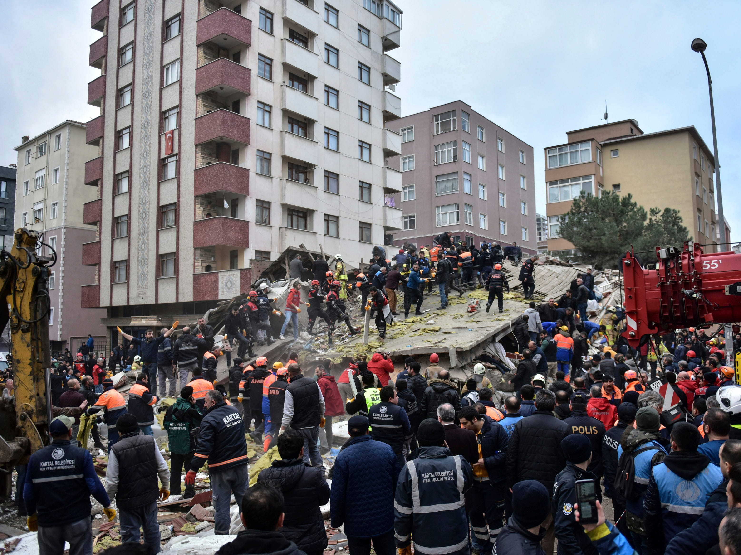 Rescue workers and people try to remove debris of an eight-story building which collapsed in Istanbul, Wednesday, Feb. 6, 2019.