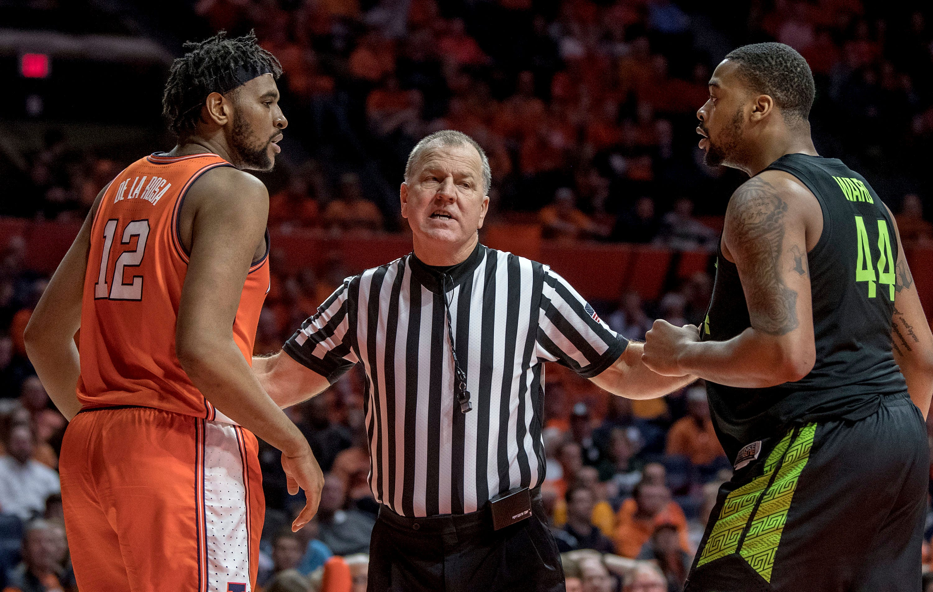 An official gets between Illinois center Adonis De La Rosa and Michigan State forward Nick Ward.