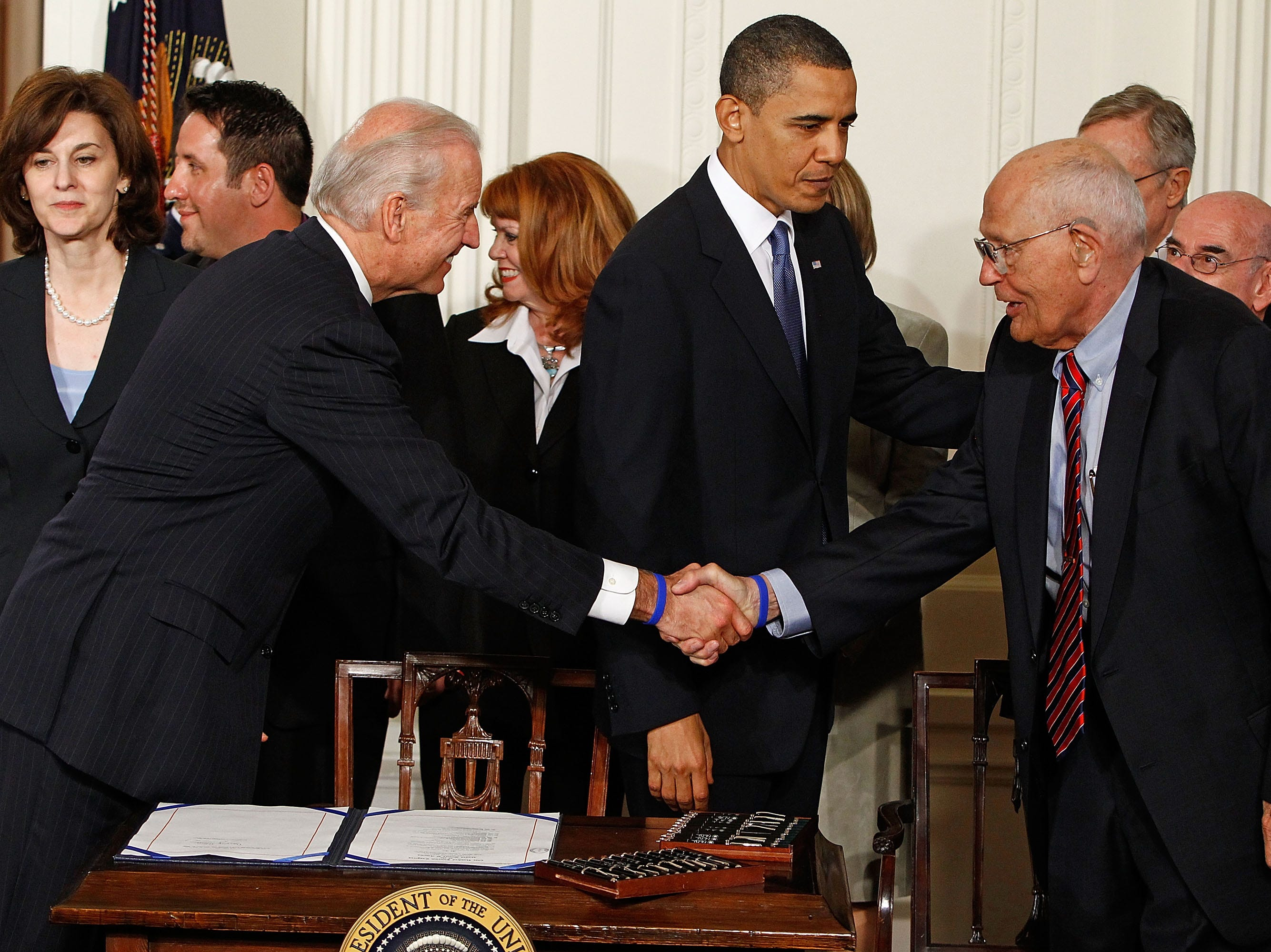 Vice President Joe Biden and President Barack Obama shake hands with Dingell before Obama signs the Affordable Health Care for America Act during a ceremony in the White House March 23, 2010. Dingell had introduced national health insurance legislation for more than 50 years before he finally saw it become law.