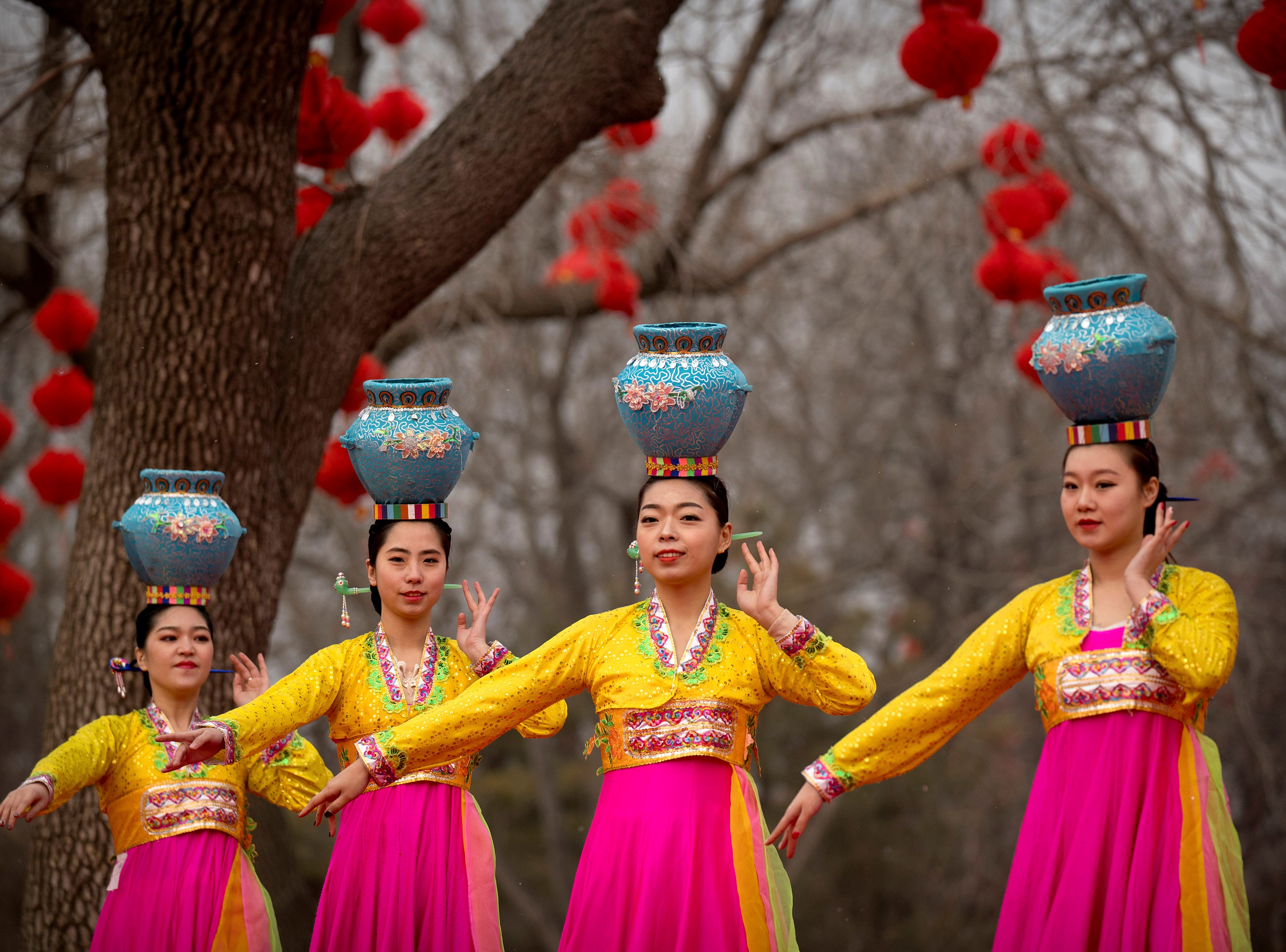 Dancers in traditional ethnic clothing perform at a temple fair at Longtan Park in Beijing, Wednesday, Feb. 6, 2019. China is celebrating the second day of the Lunar New Year on Tuesday, the Year of the Pig on the Chinese zodiac.