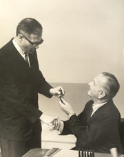 Dingell kept a personal and professional photo archive in his office, including this photo of President Lyndon Johnson handing him a pen after signing a bill.