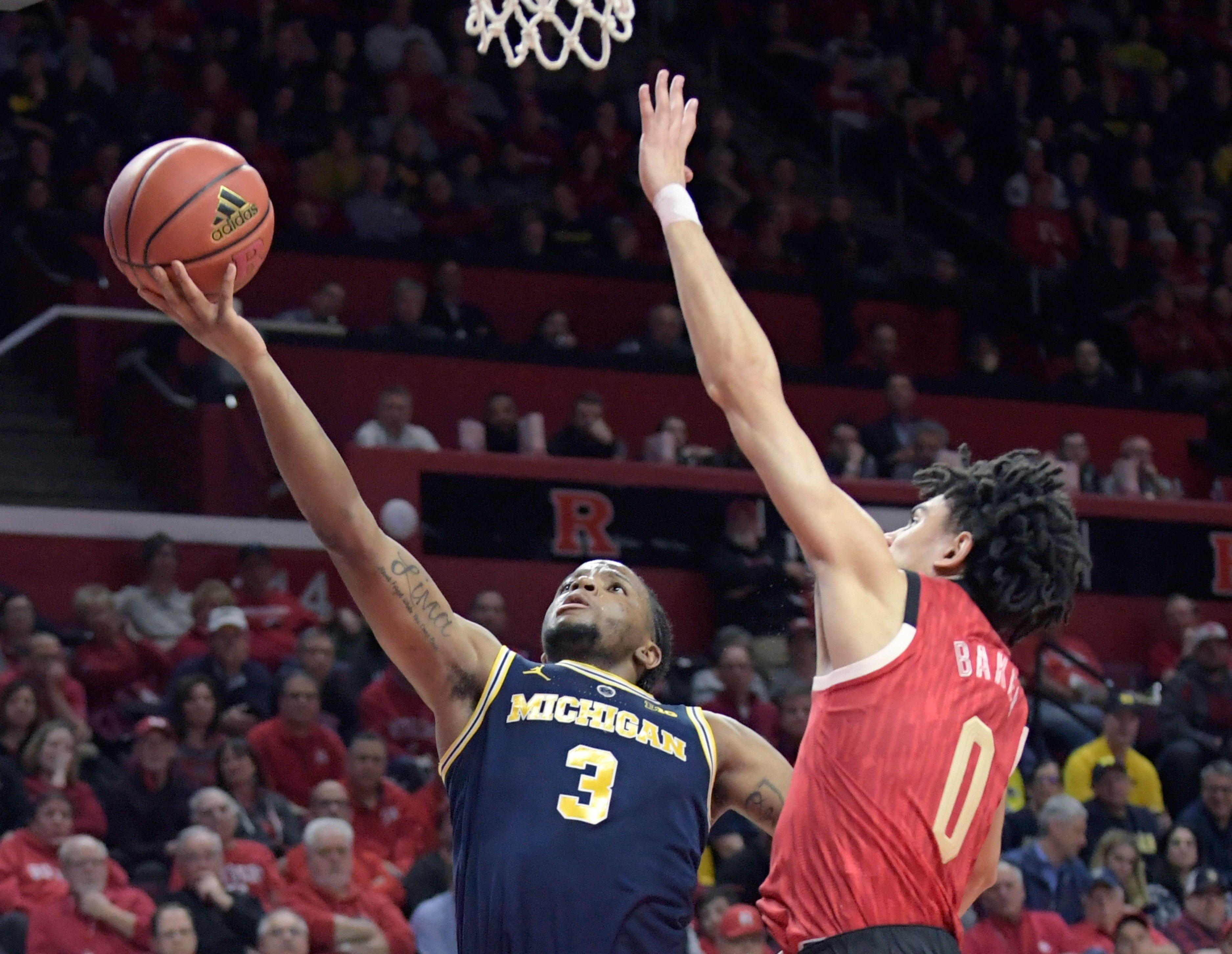 Michigan's Zavier Simpson drives to the rim against Rutgers' Geo Baker in Tuesday's 77-65 win.