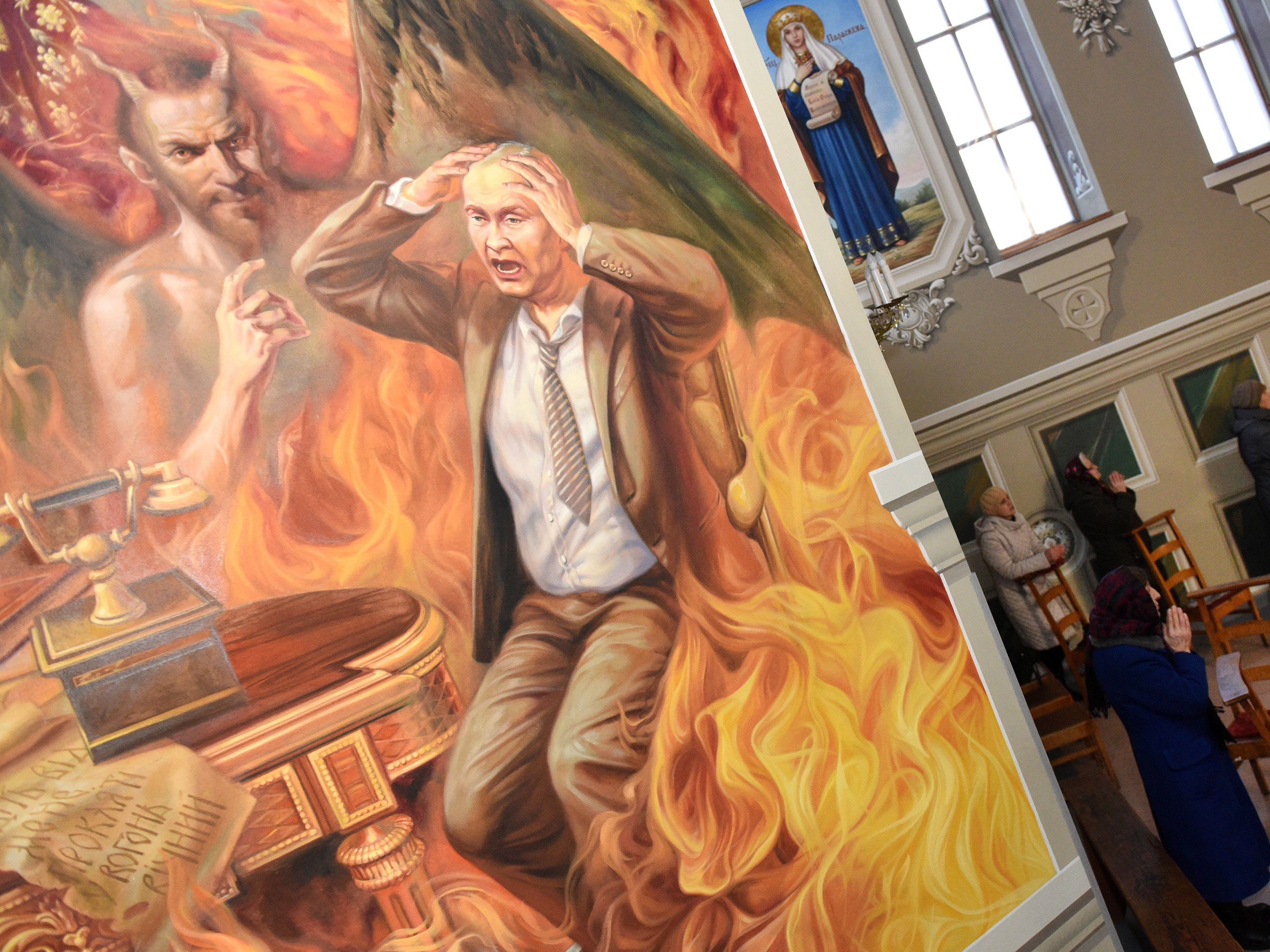 """Believers of the Byzantine-rite Catholic Church of the Ukraine pray close to a frescos entitled  """"Judgement Last Day"""" in the St. Josaphat Cathedral in Chervonograd on February 6, 2019.  The fresco shows Russian President Vladimir Putin burning in hellfire."""