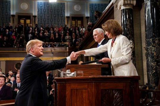 President Donald Trump shakes hands with House Speaker Nancy Pelosi as Vice President Mike Pence looks on, as he arrives in the House chamber before giving his State of the Union address to a joint session of Congress, Tuesday, Feb. 5, 2019 at the Capitol in Washington.