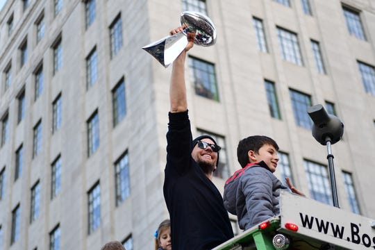 Tom Brady displays the Vince Lombardi trophy during the Super Bowl parade.