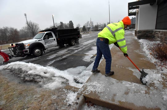 Greenline Turf Services owner Nick Frink, of Memphis, Michigan, scrapes ice off the sidewalk in front of Lakestone Bank & Trust in Armada during an ice storm Wednesday.