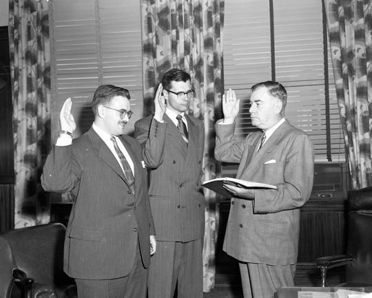 In 1953, John Dingell Jr., center, and William J. Coughlin, left, take the oath of office from Gerald O'Brien. Dingell would serve as an assistant prosecuting attorney for Wayne County until 1955.