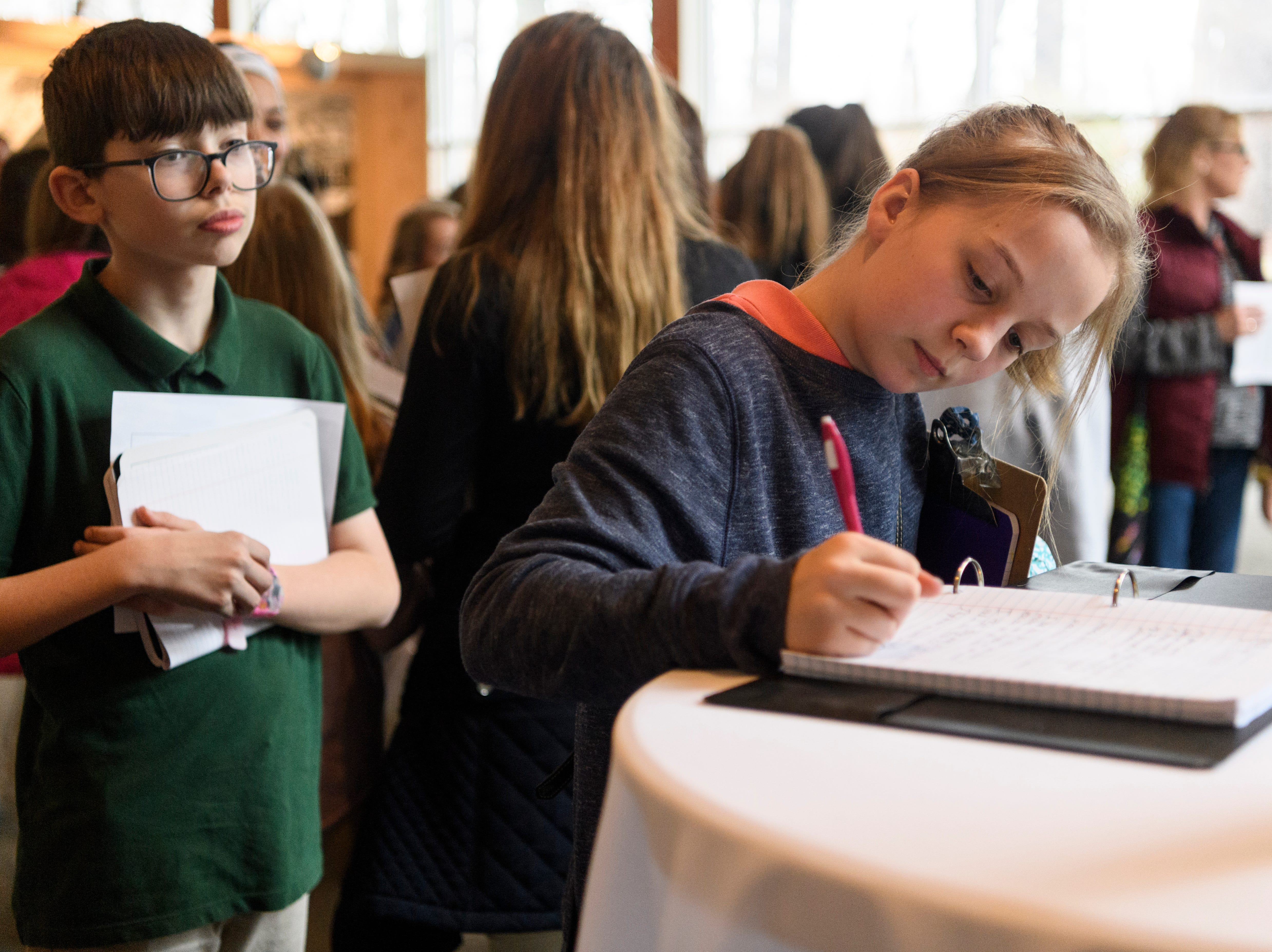 """Hannah Brown, right, Thompkins Middle School sixth-grader, writes a comment about her thoughts on """"A New Generation Remembers"""" Holocaust exhibit as classmate Griffin Dunville, left, waits for his turn at Temple Adath B'nai Israel in Evansville, Ind., Wednesday, Feb. 6, 2019."""