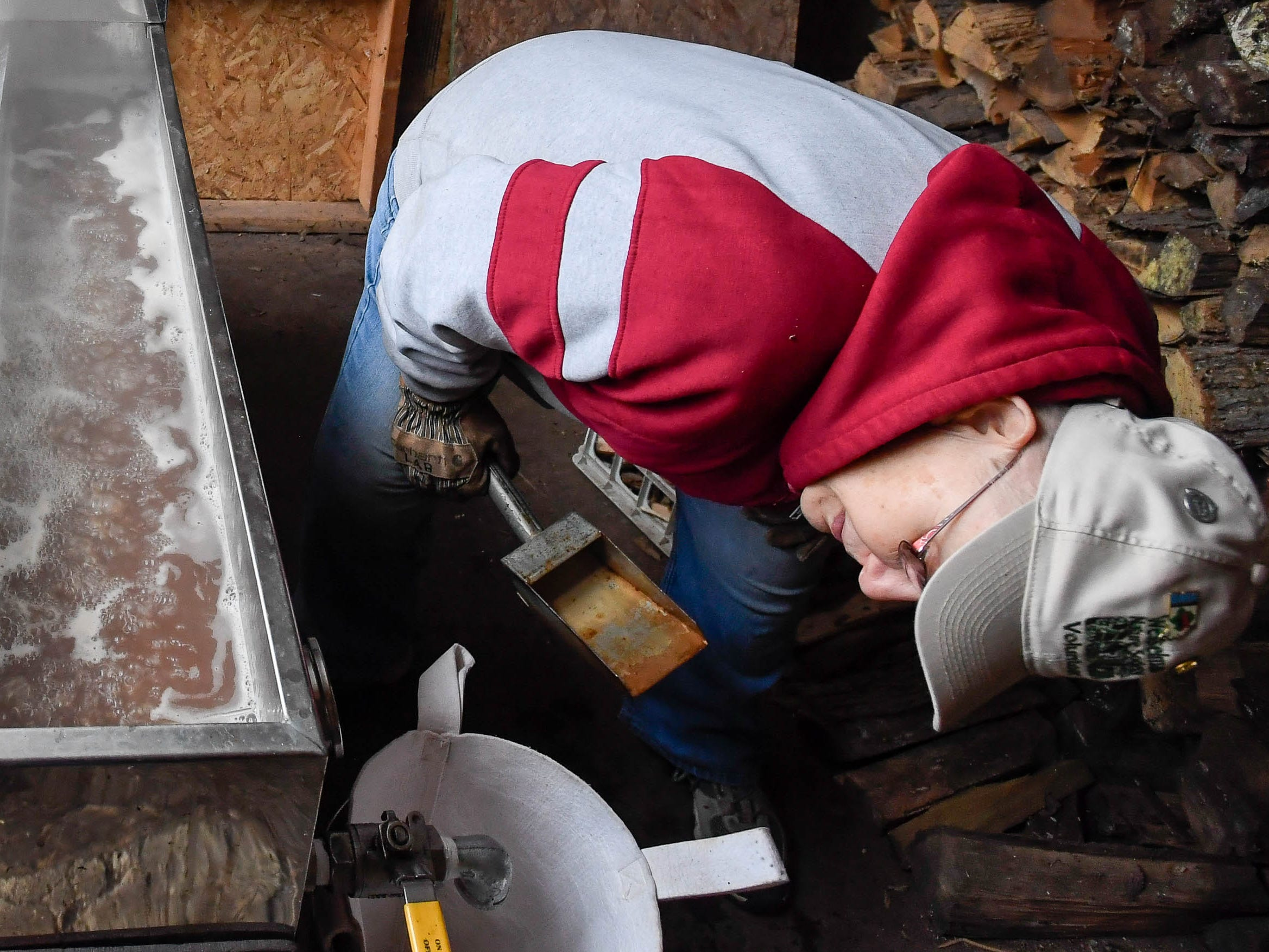 Volunteer LeeAnne Bruner reads the thermometer on the evaporator as she cooks maple syrup, as maple syrup production is under way at the Wesselman Woods Nature Preserve for the park's Annual Sugarbush Festival, Tuesday. Bruner has been cooking maple syrup at the park for over 30 years, February 5, 2019.