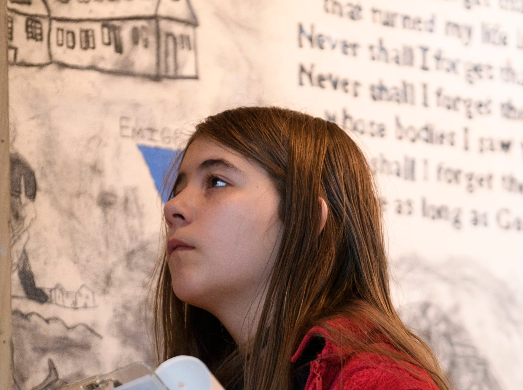"""Isabella Nellis, a Thompkins Middle School student, reads more about a mural on display with the """"A New Generation Remembers"""" Holocaust exhibit at Temple Adath B'nai Israel in Evansville, Ind., Wednesday, Feb. 6, 2019."""