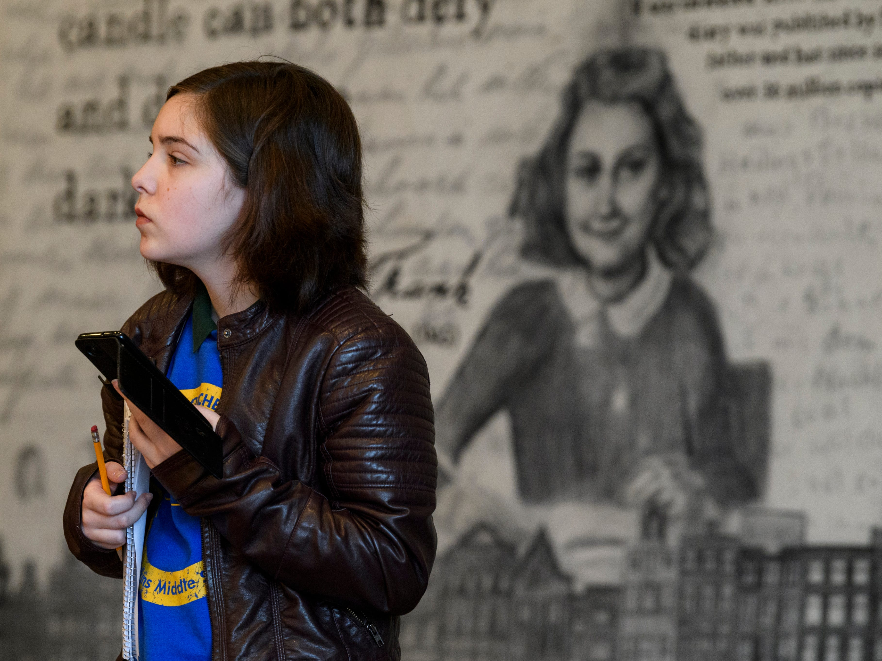 """Emma Sallee, Thompkins Middle School sixth-grader from Rebekah Hodge's class, stands in front of a mural depicting Anne Frank, one of the most discussed Jewish victims of the Holocaust, while viewing the """"A New Generation Remembers"""" Holocaust exhibit at Temple Adath B'nai Israel in Evansville, Ind., Wednesday, Feb. 6, 2019."""