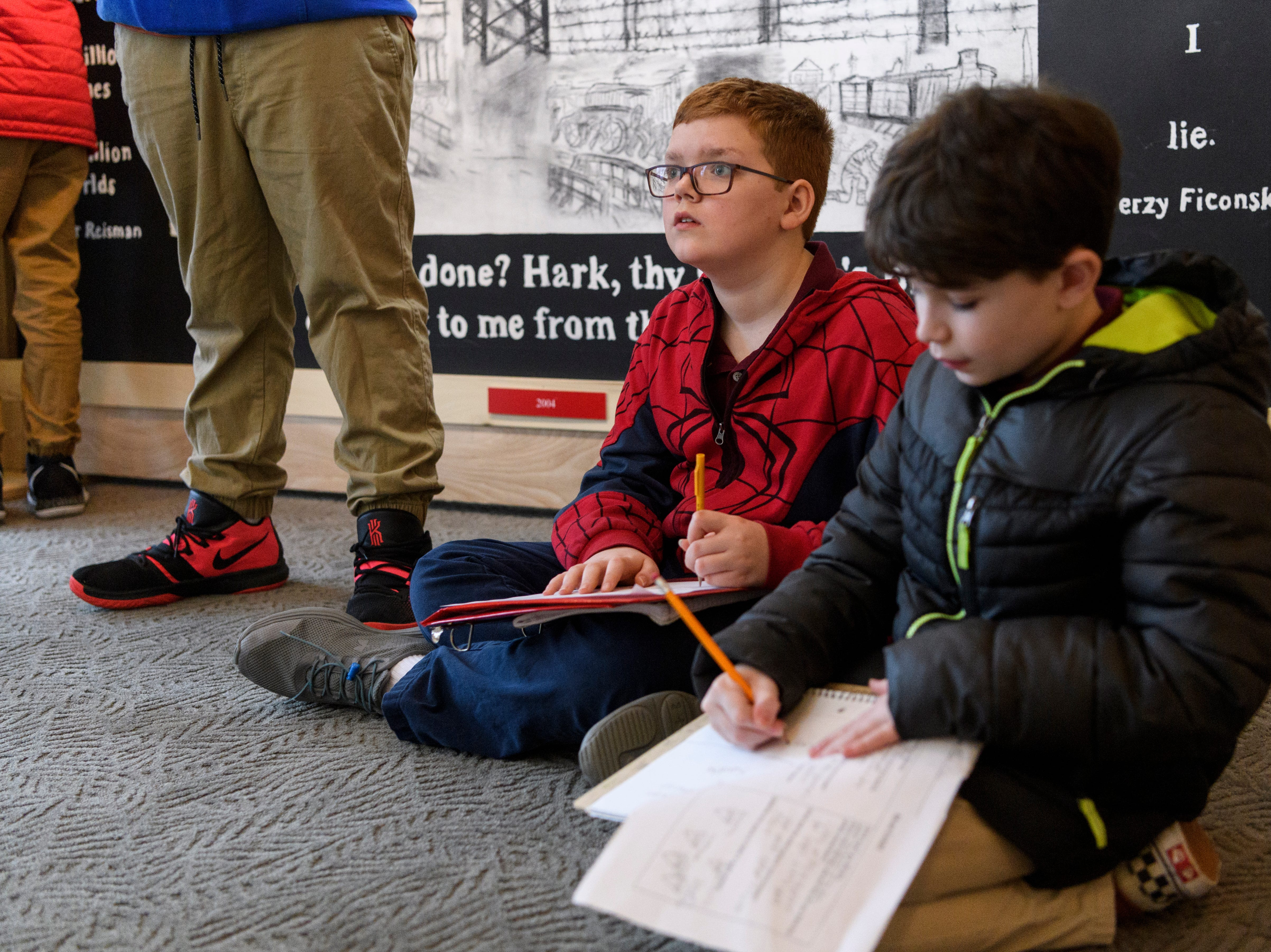 """Jordan Box, left, and Aidan Fisher, right, Thompkins Middle School sixth-graders, observe and take notes on the murals displayed in the """"A New Generation Remembers"""" Holocaust exhibit at Temple Adath B'nai Israel in Evansville, Ind., Wednesday, Feb. 6, 2019."""
