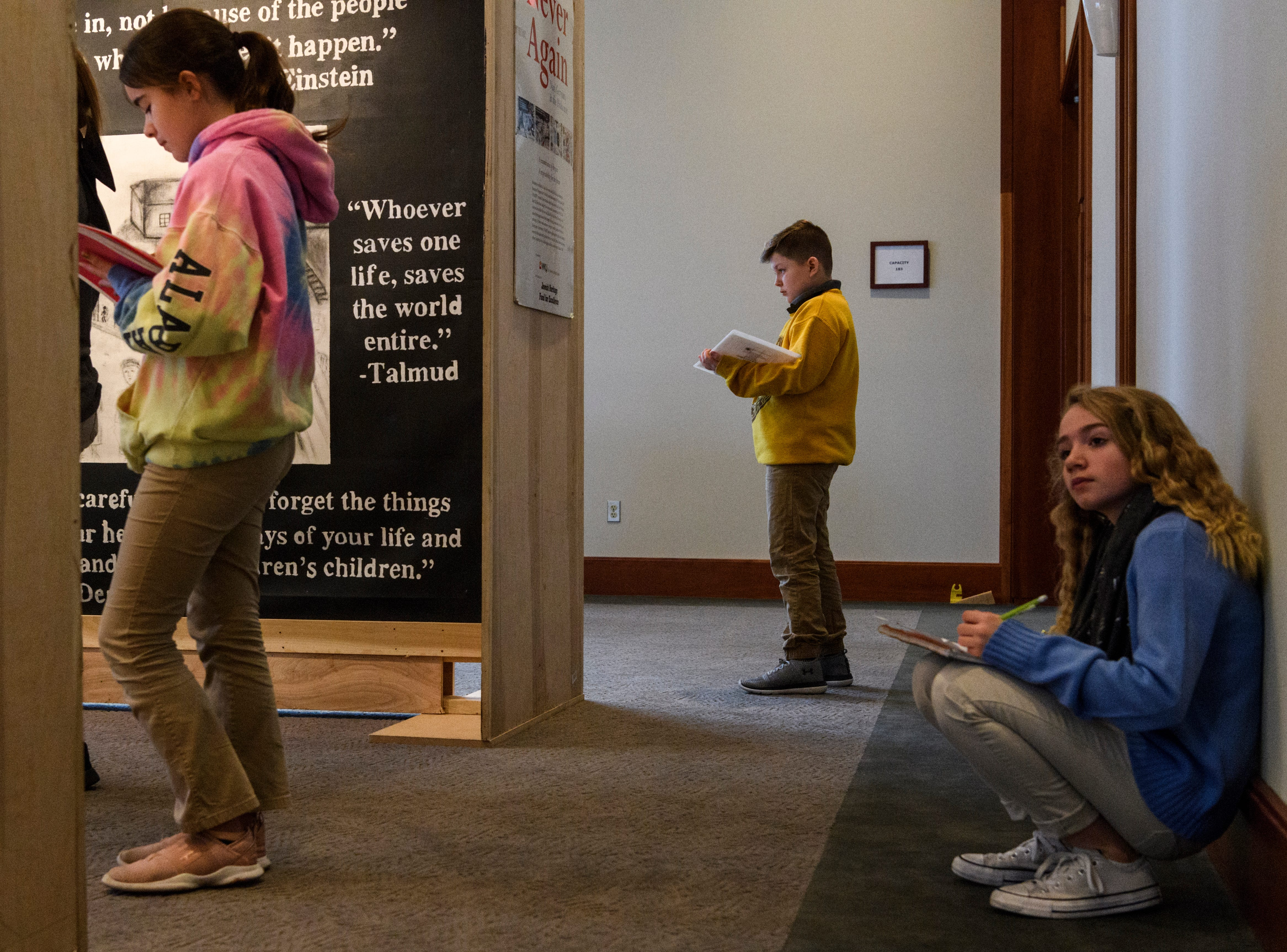 """Thompkins Middle School sixth-grade students Addison Sanders, from left, Gavin Podewils, Sydnee Robinson take notes as they view the """"A New Generation Remembers"""" Holocaust exhibit at Temple Adath B'nai Israel in Evansville, Ind., Wednesday, Feb. 6, 2019."""