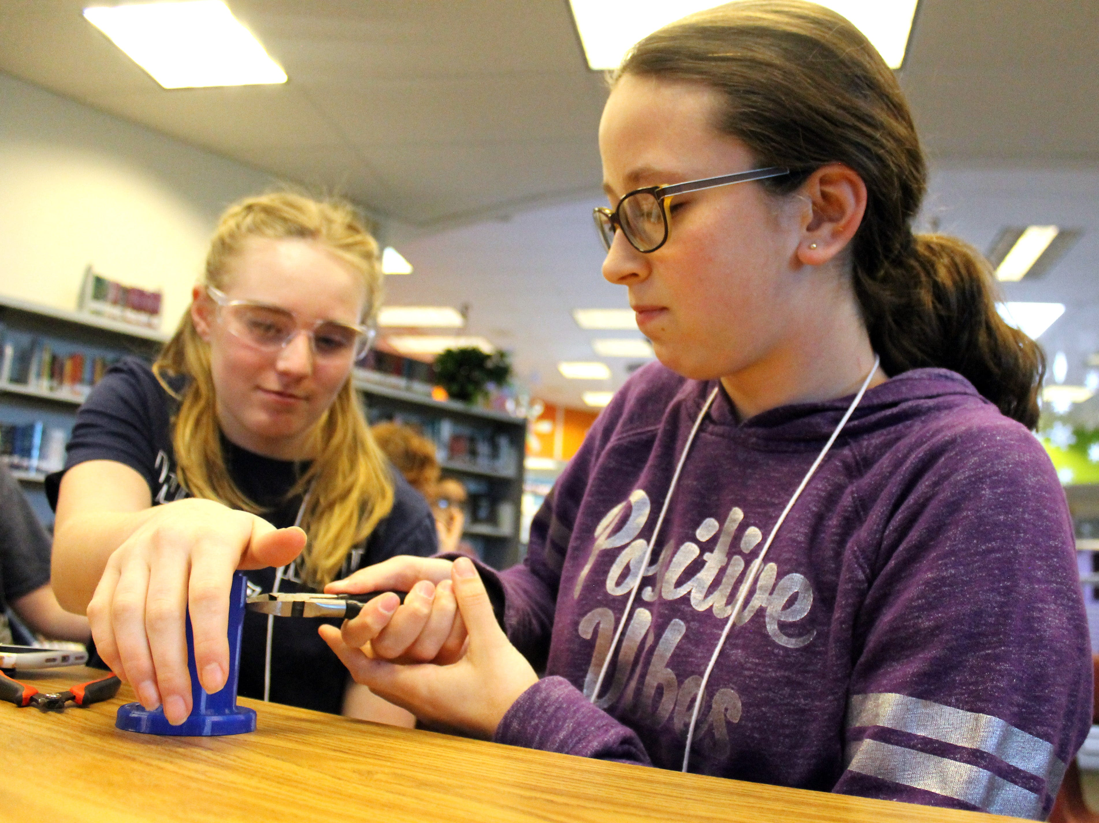 Bronte Wayne, left, and Kylie Perez work together to set up a lantern for Engineering Brightness Feb. 4, 2019 at Preston Middle School. The group works to engineer 3D printed, sustainable lanterns and distributes  them to people without reliable electricity worldwide.