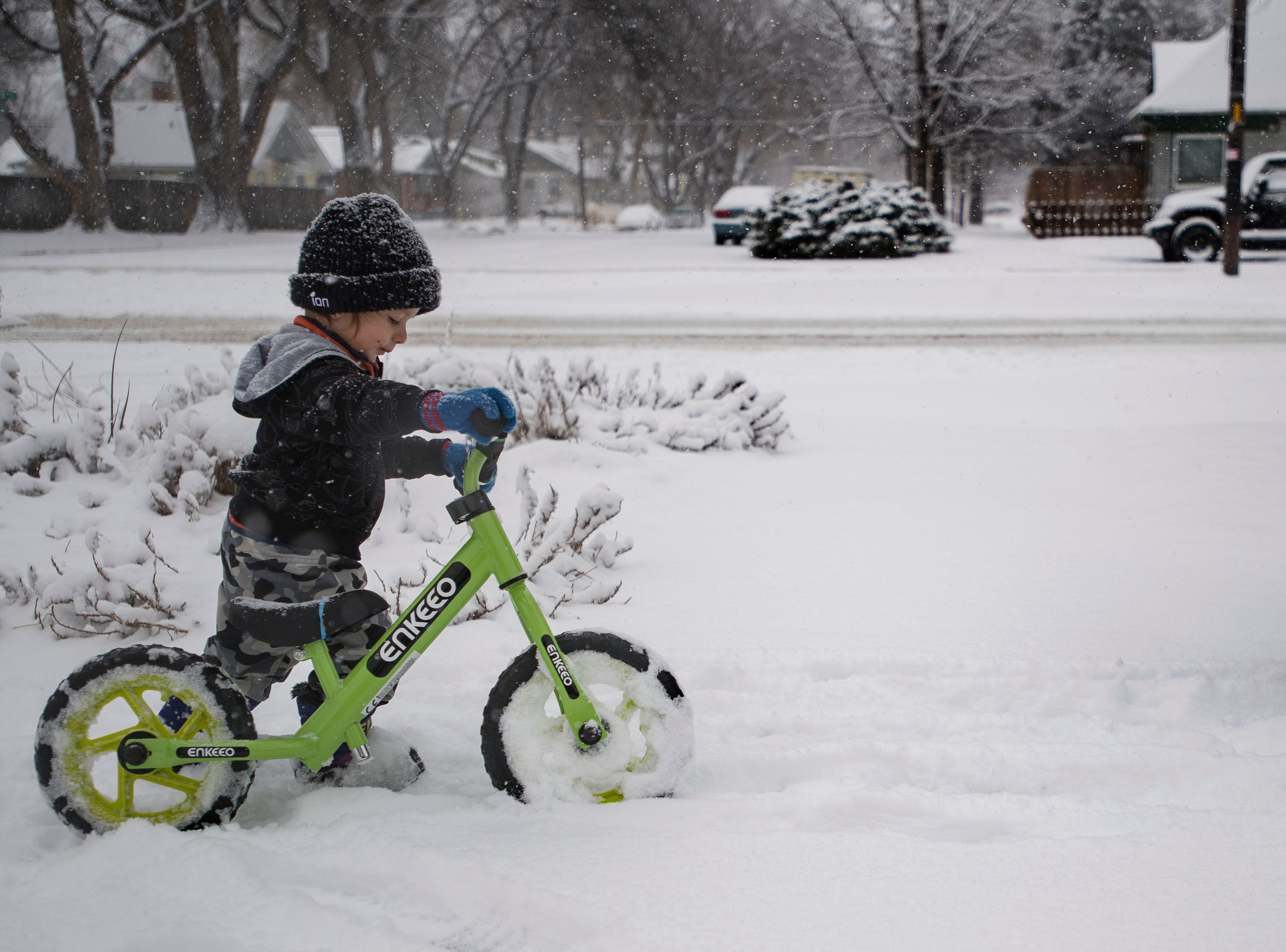 Ren Koning, 2, walks the bike that he got from his grandmother for Christmas through the snow with Reisha Koning on Wednesday, Feb. 6, 2019, in Fort Collins, Colo.