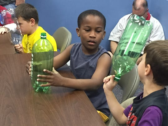 Julian Jr. participates in an arts and craft project led by his mom.