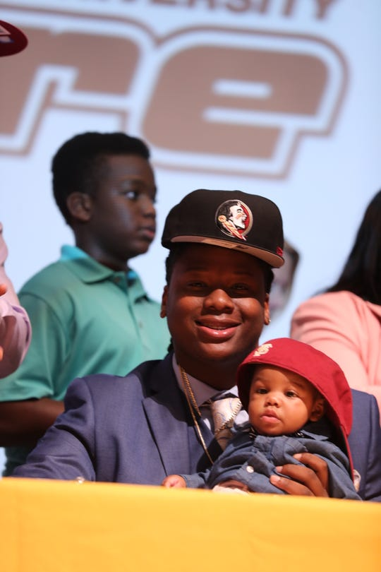 Lehigh Senior High School defensive end Quashon Fuller decides to sign with Florida State on National Signing Day. He is pictured holding his five-month-old nephew, Kyrie Gloster.