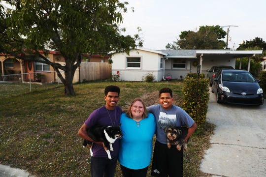 Nicole Schofield stands for a portrait with her boys, Byron and LaSean Adams in front of her newly renovated home near Franklin Park Elementary School in the Dunbar neighborhood of Fort Myers. Schofield bought the home that was renovated by the Patricia Botell Foundation. The purpose of the Foundation is to renovate once condemned or run down properties and sell them at affordable prices.