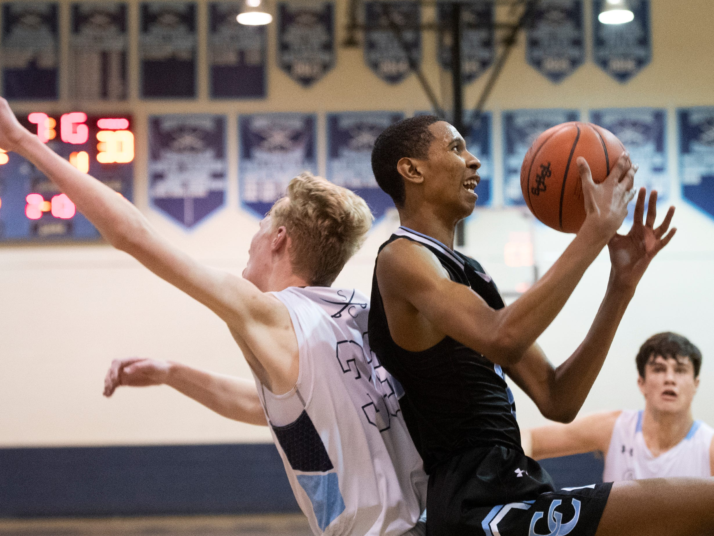 Christ Church Episcopal School's John Butler (13) has the ball after competing with Southside Christian High School's Ian Thomson (33) for a rebound at Southside Christian High School Tuesday, Feb. 5, 2019.
