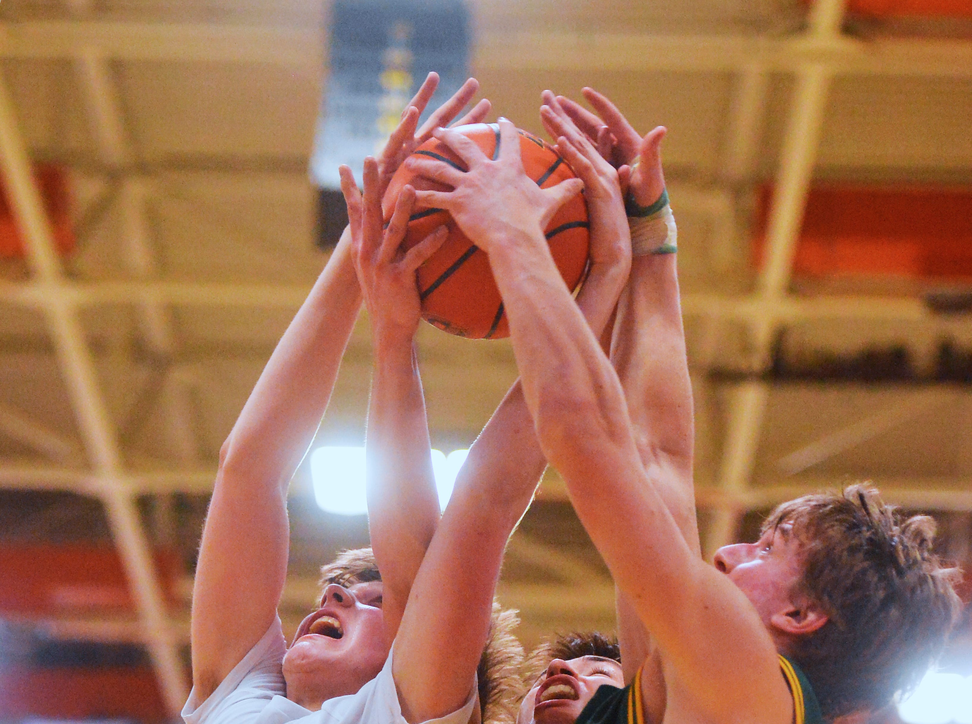 Great Falls High's Drew Wyman, left,  battles for a rebound with CMR's Bryce Depping, center, and Cason Taylor during the boys crosstown basketball game in the Swarthout Fieldhouse, Tuesday.