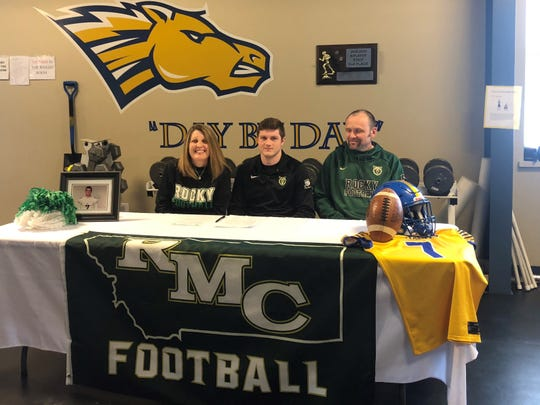 Great Falls Central's Riley Dickinson, flanked by his parents Sara and Tracy Murphy, after signing his NAIA national letter-of-intent to attend Rocky Mountain College in Billings this fall.