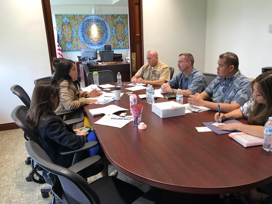 This photo, released Feb. 5 by Marine Corps Activity Guam, shows a meeting that morning at Speaker Tina Muna Barnes' office to provide an update on the military buildup. At left are Barnes, in tan jacket, and Sen. Regine Biscoe Lee, using a smartphone. At the military's request, the speaker's office has not released informational material provided by the military during that meeting.