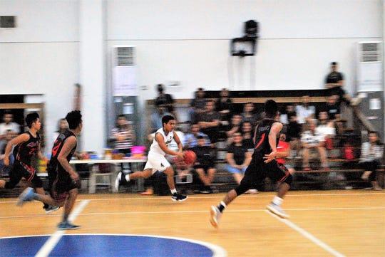 St. Paul's Kris Calairo races downcourt on a fast break against Simon Sanchez in their IIAAG High School Boys Basketball game Feb. 6 at St. Paul.