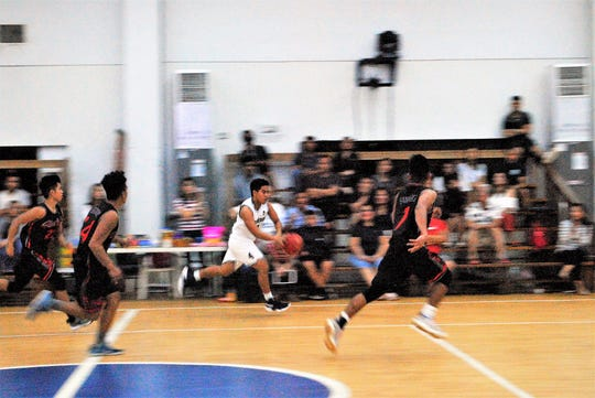 St. Paul's Kris Calairo races downcourt on a fast break against Simon Sanchez in their IIAAG High School Boys Basketball game Feb. 6 at St. Paul.