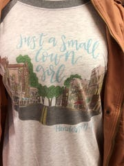 "A custom-made girl's raglan featuring artwork based on photographs of the 100 block of North Main Street and the declaration, ""Just a small town girl,"" is among the more popular items at Beachbum Farms gift shop in that very block."