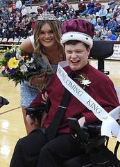 Homecoming Queen Hannah Watkins poses with classmate Seth Liles during halftime at Tuesday night's game. She and King Will Steiner decided to share their royal spotlight with their classmate, who was also part of the Senior homecoming court.