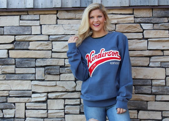 Torunn Stuen Johnson models a custom-made Henderson sweatshirt with an old-fashioned baseball jersey-style logo that is available at the Henderson Tourist Commission gift shop in The Depot.