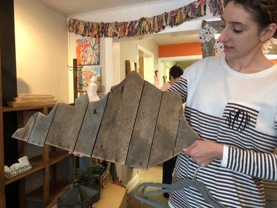 Sarah Osborne of Beachbum Farms gift shop on Main Street holds a hand-cut wooden outline of the state of Kentucky, one of a variety of locally hand-crafted items the shop stocks.
