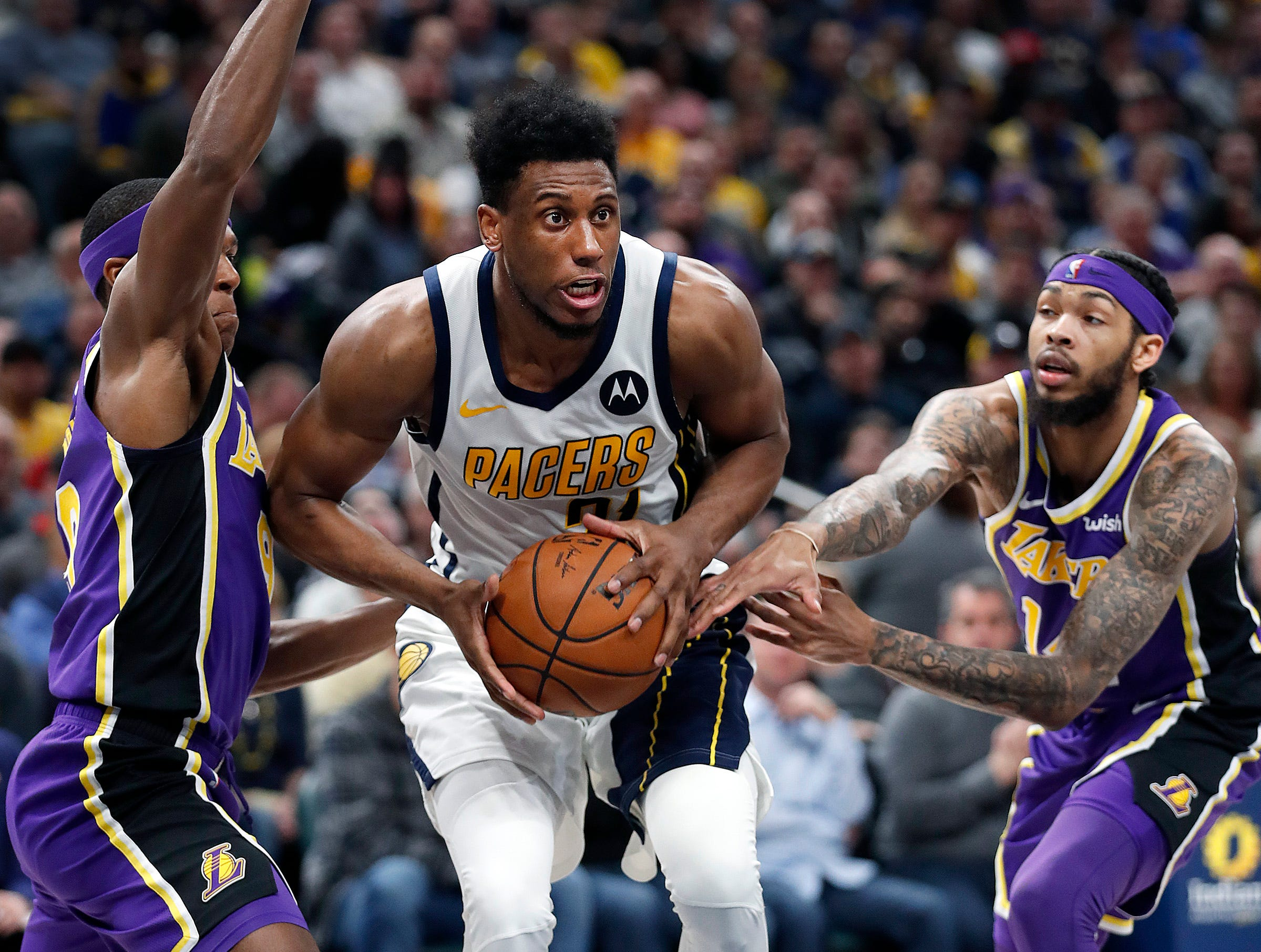 Indiana Pacers forward Thaddeus Young (21) drives between Los Angeles Lakers forward Brandon Ingram (14) and Rajon Rondo (9) in the first half of their game at Bankers Life Fieldhouse on Tuesday, Feb. 5, 2019.