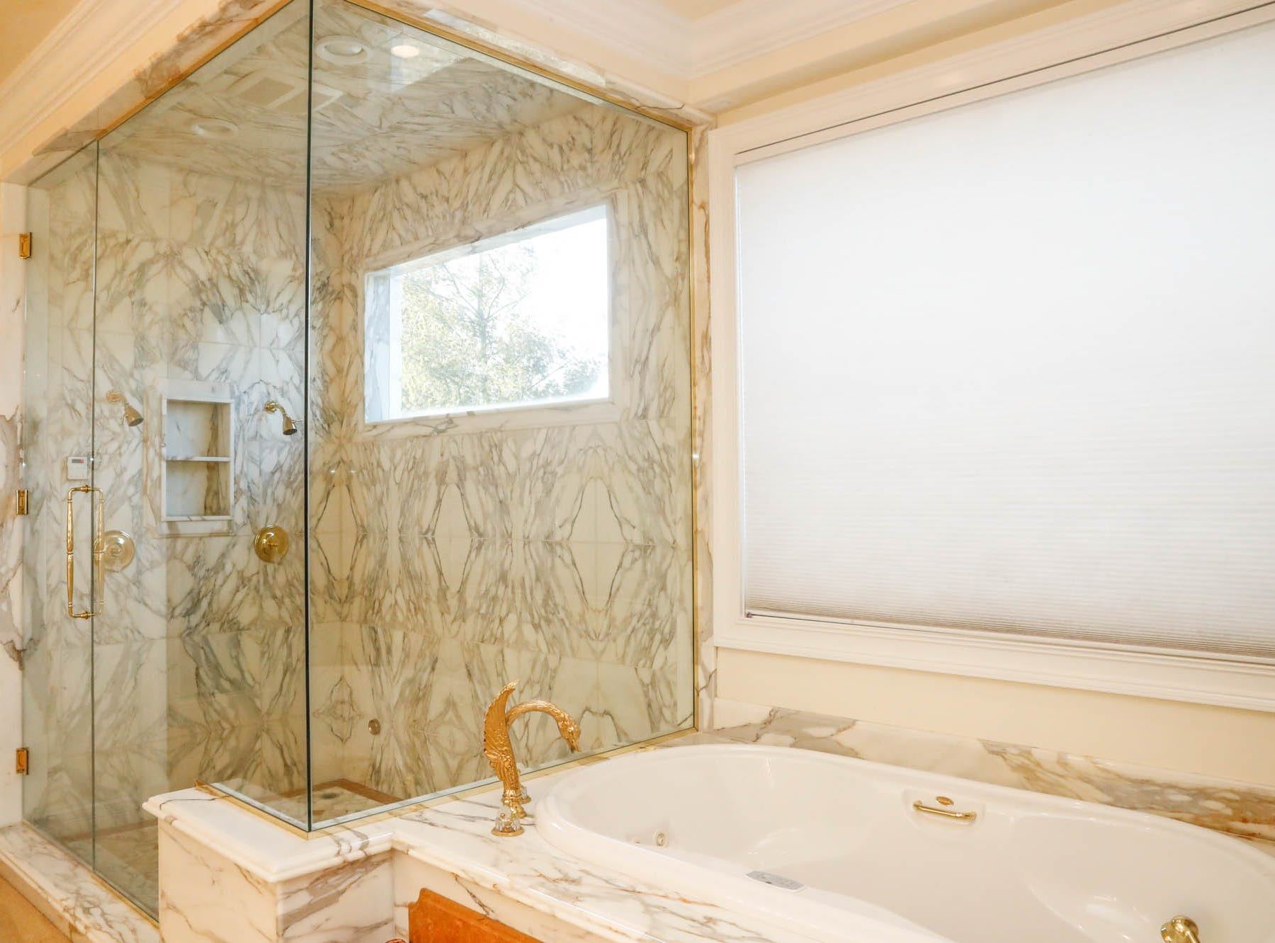 A first-floor master bath, one of two in the home, features gold accents, a whirlpool tub, and all the storage space you could ask for, at a Greenwood home up for sale at 1216 Stone Ridge Court, Greenwood, Ind. on Wednesday, Jan. 30, 2019. The home features 8,234 square feet, four bedrooms, two master suites, a 10 car garage, and an exercise room.
