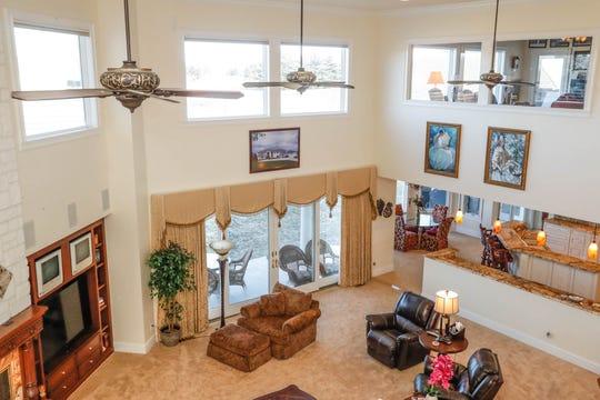 A loft provides a bird's-eye view of an open floor plan living room.