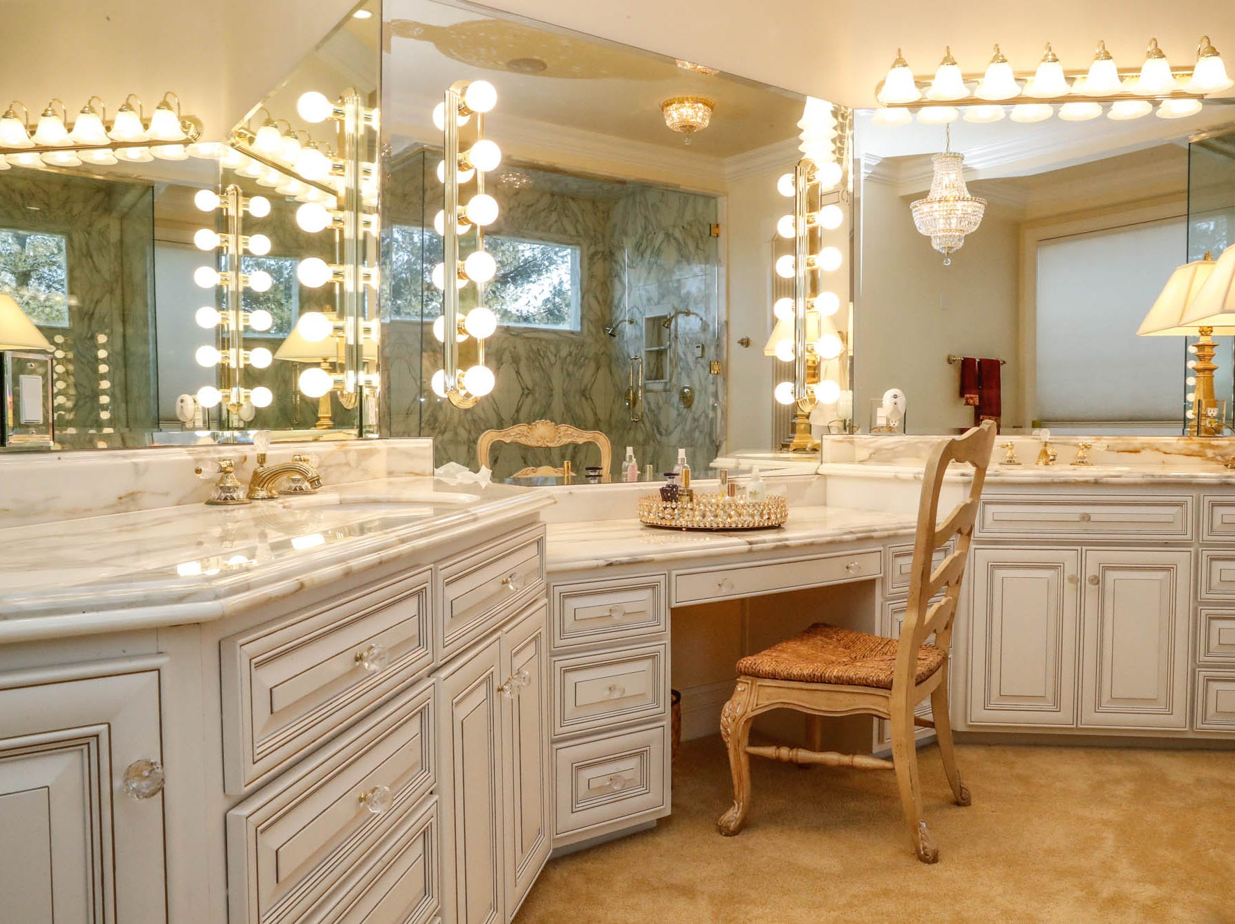 A first-floor master bath, one of two in the home, features vanity lighting, gold accents, a whirlpool tub, and all the storage space you could ask for, at a Greenwood home up for sale at 1216 Stone Ridge Court, Greenwood, Ind. on Wednesday, Jan. 30, 2019. The home features 8,234 square feet, four bedrooms, two master suites, a 10 car garage, and an exercise room.
