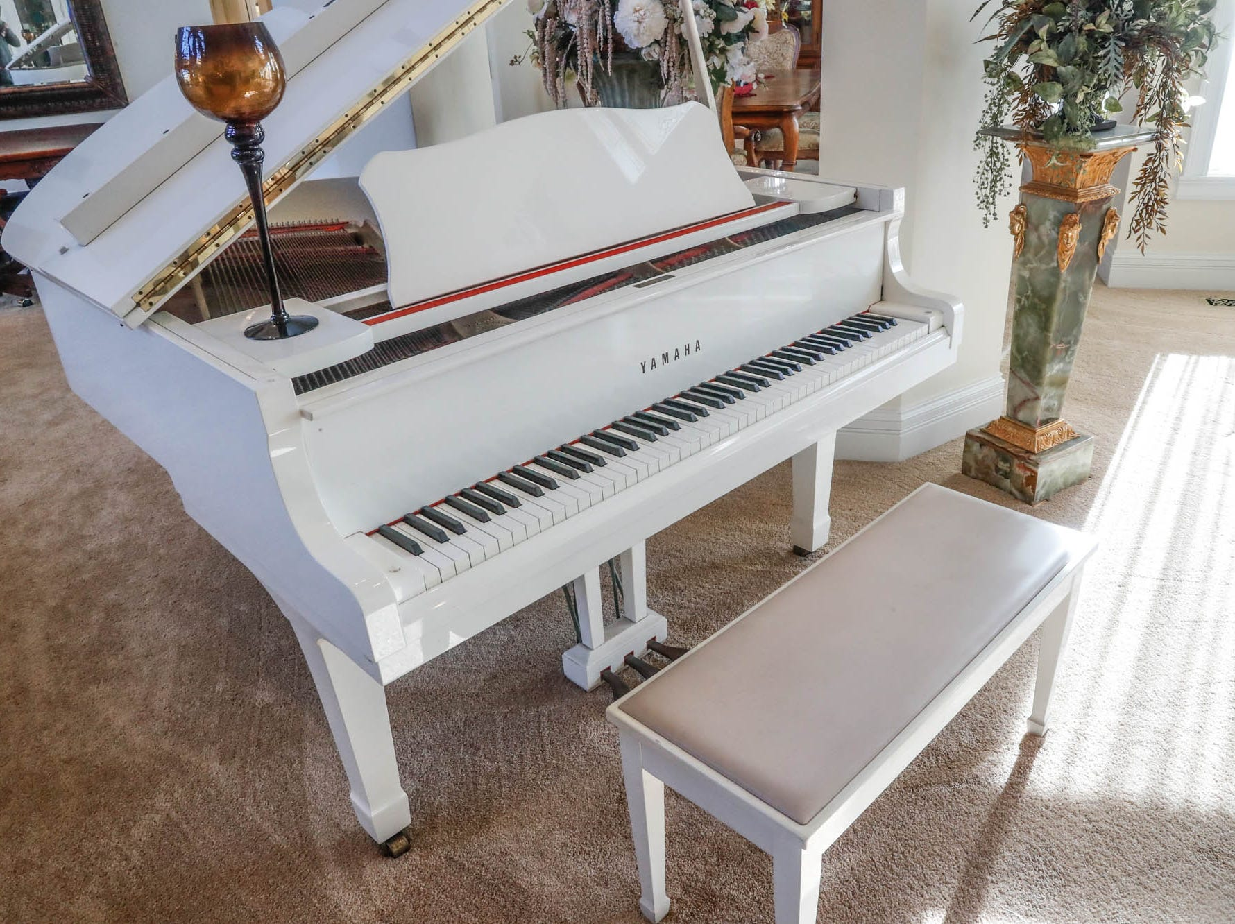 A Greenwood home up for sale at 1216 Stone Ridge Court, Greenwood, Ind., features a white piano in the open living room on Wednesday, Jan. 30, 2019. The home features 8,234 square feet, four bedrooms, two master suits, a 10 car garage, and exercise room.
