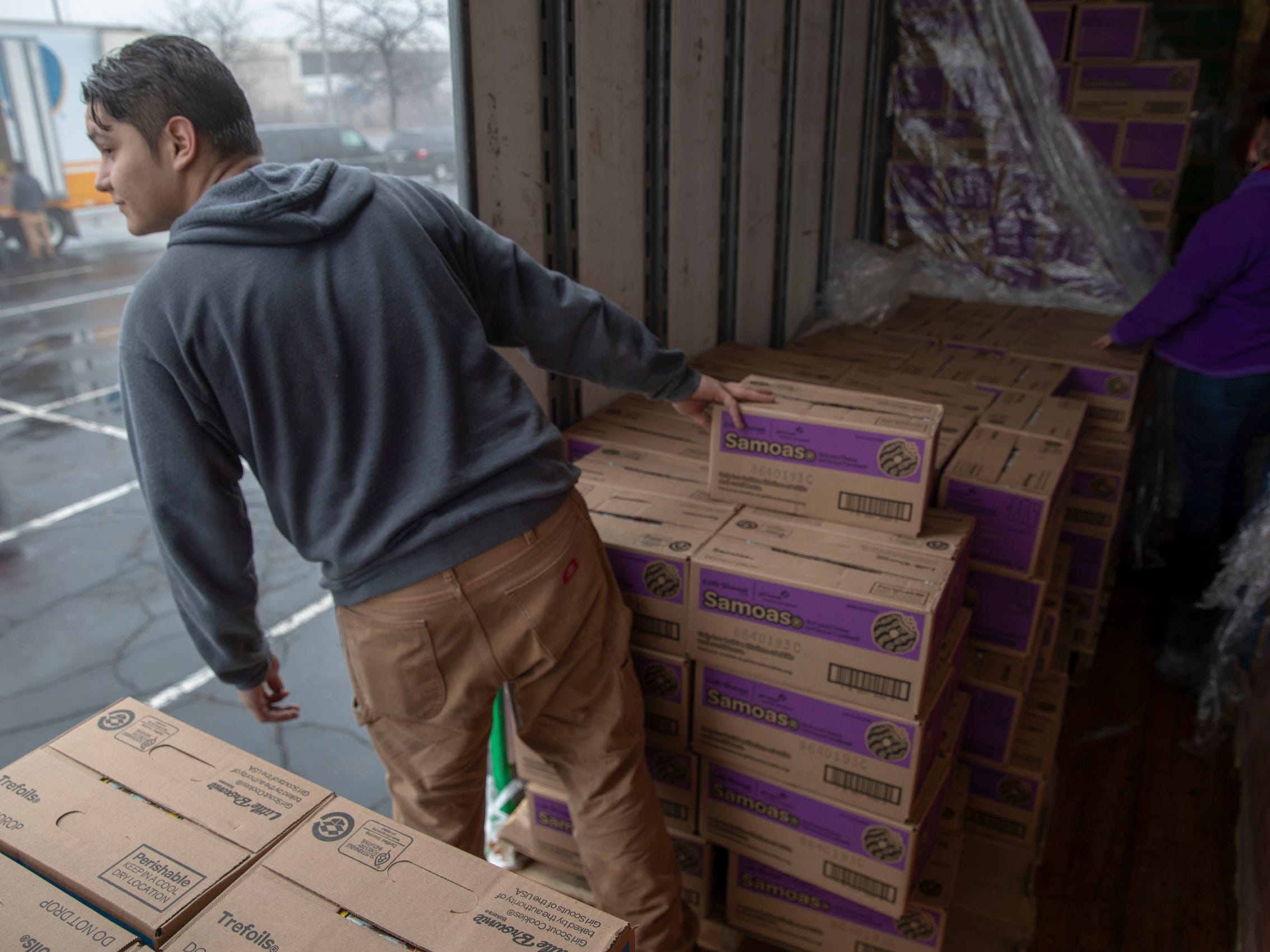 Nathaniel Scaggs, Indianapolis, looks for the next car to roll up during distribution for Girl Scout Cookies in Indianapolis, Wednesday, Feb. 6, 2019. The cookies will start to appear locally on the weekend, and should last into mid-March.