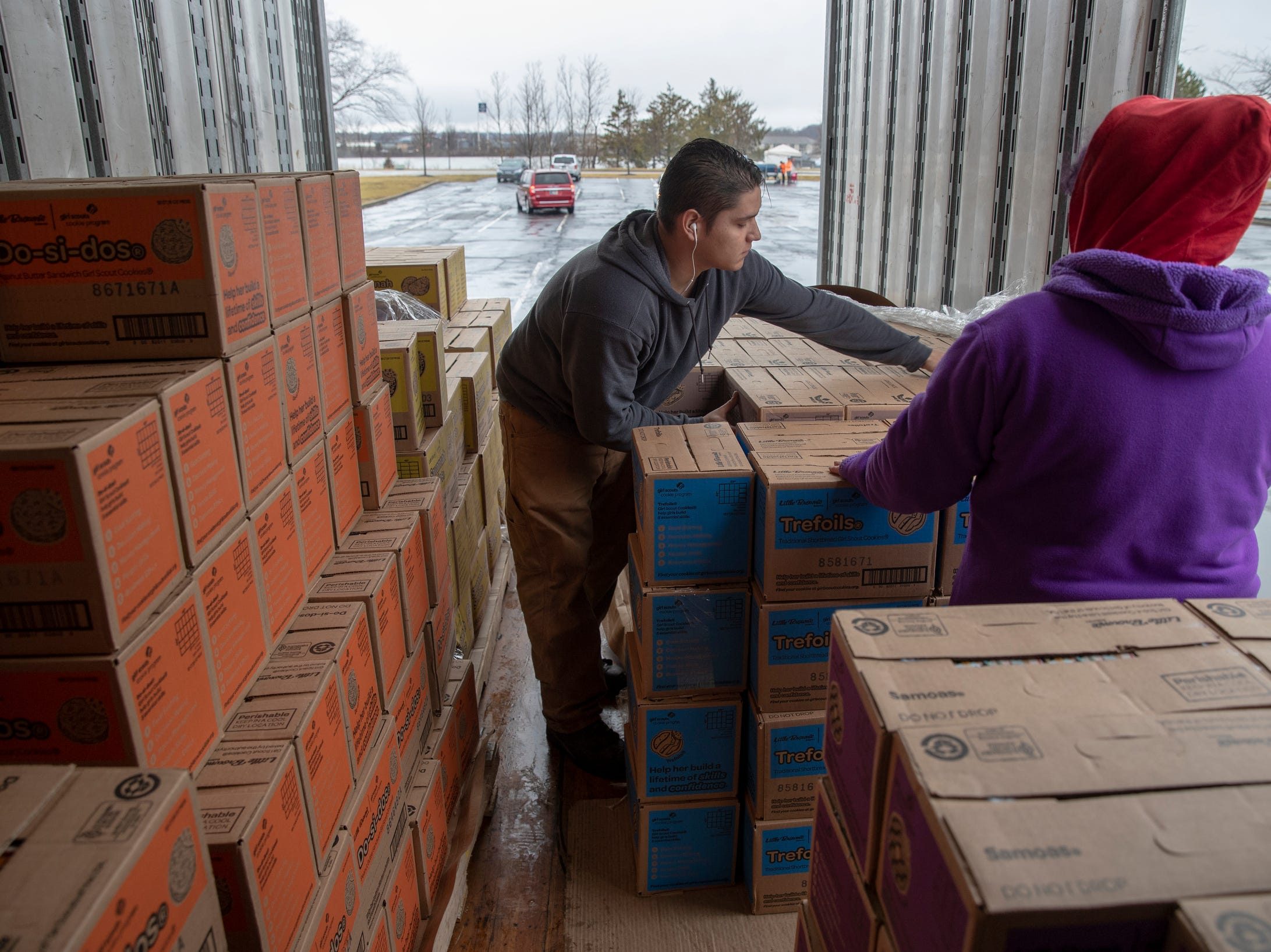 Nathaniel Scaggs (left), with mother Misty Scaggs, both of Indianapolis, work the distribution for Girl Scout Cookies in Indianapolis, Wednesday, Feb. 6, 2019. The cookies will start to appear locally on the weekend, and should last into mid-March.