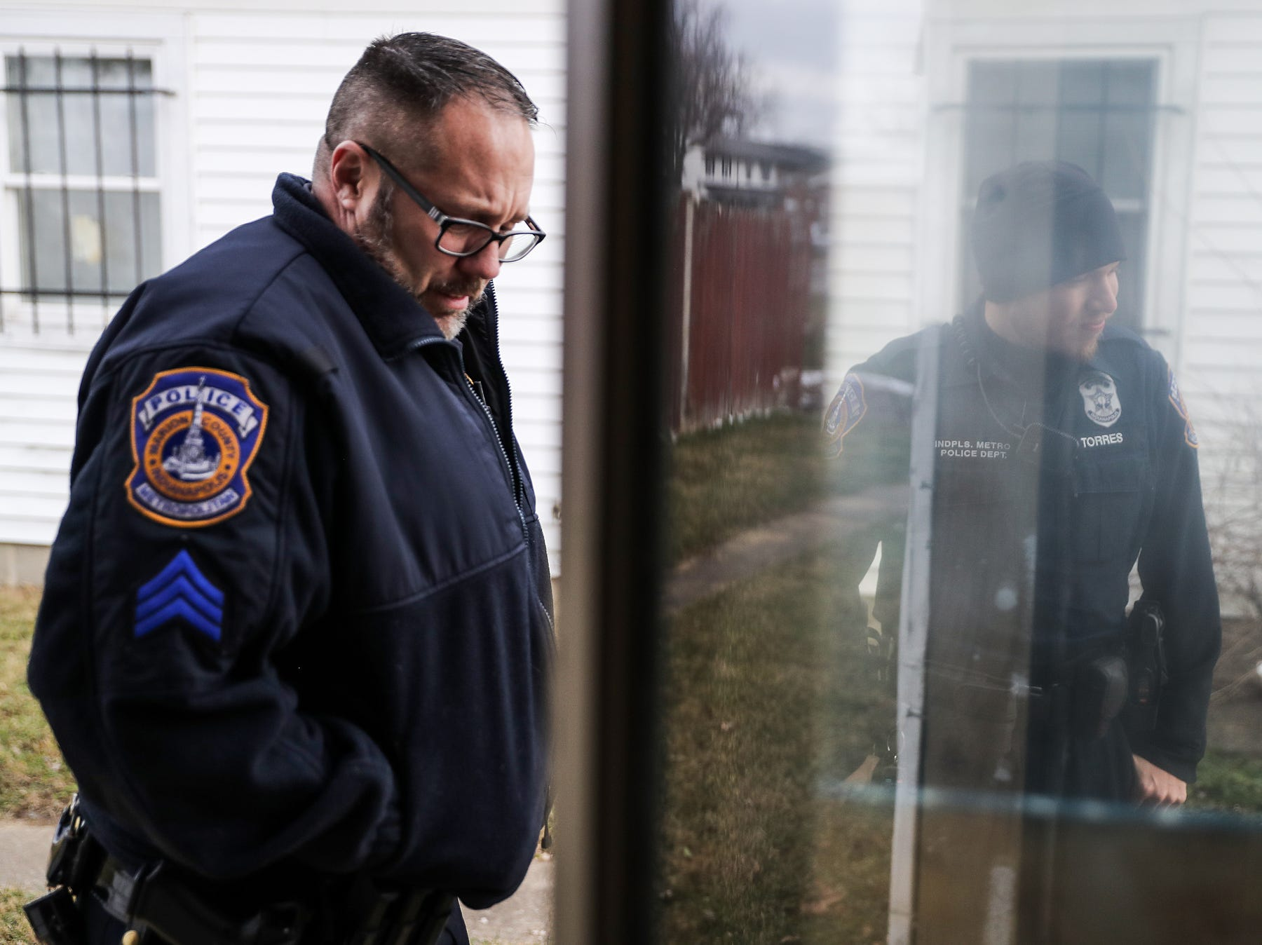 From left, Sgt. Aaron Sparks and IMPD officer Jeremy Torres stand outside of an abandoned unit on Essex Court where the body of Anthony Eldridge was found in June 2018, at the Towne and Terrace housing complex off of 42nd Street and Post Road, Saturday, Dec. 8, 2018. At one point, a camera was mounted on the back of the building to keep watch for police entering the complex.