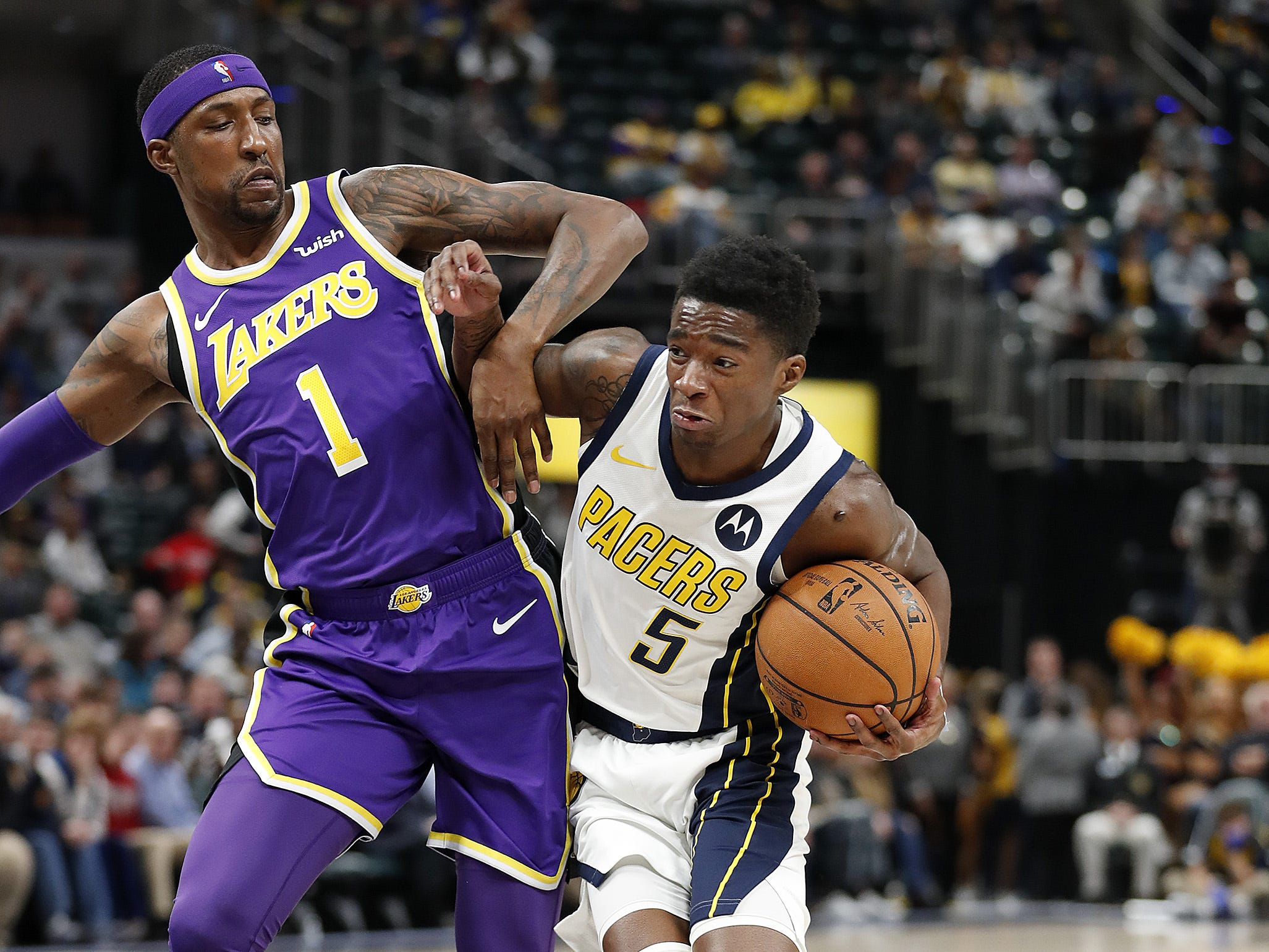 Indiana Pacers guard Edmond Sumner (5) drives on Los Angeles Lakers guard Kentavious Caldwell-Pope (1) in the second half of their game at Bankers Life Fieldhouse on Tuesday, Feb. 5, 2019.
