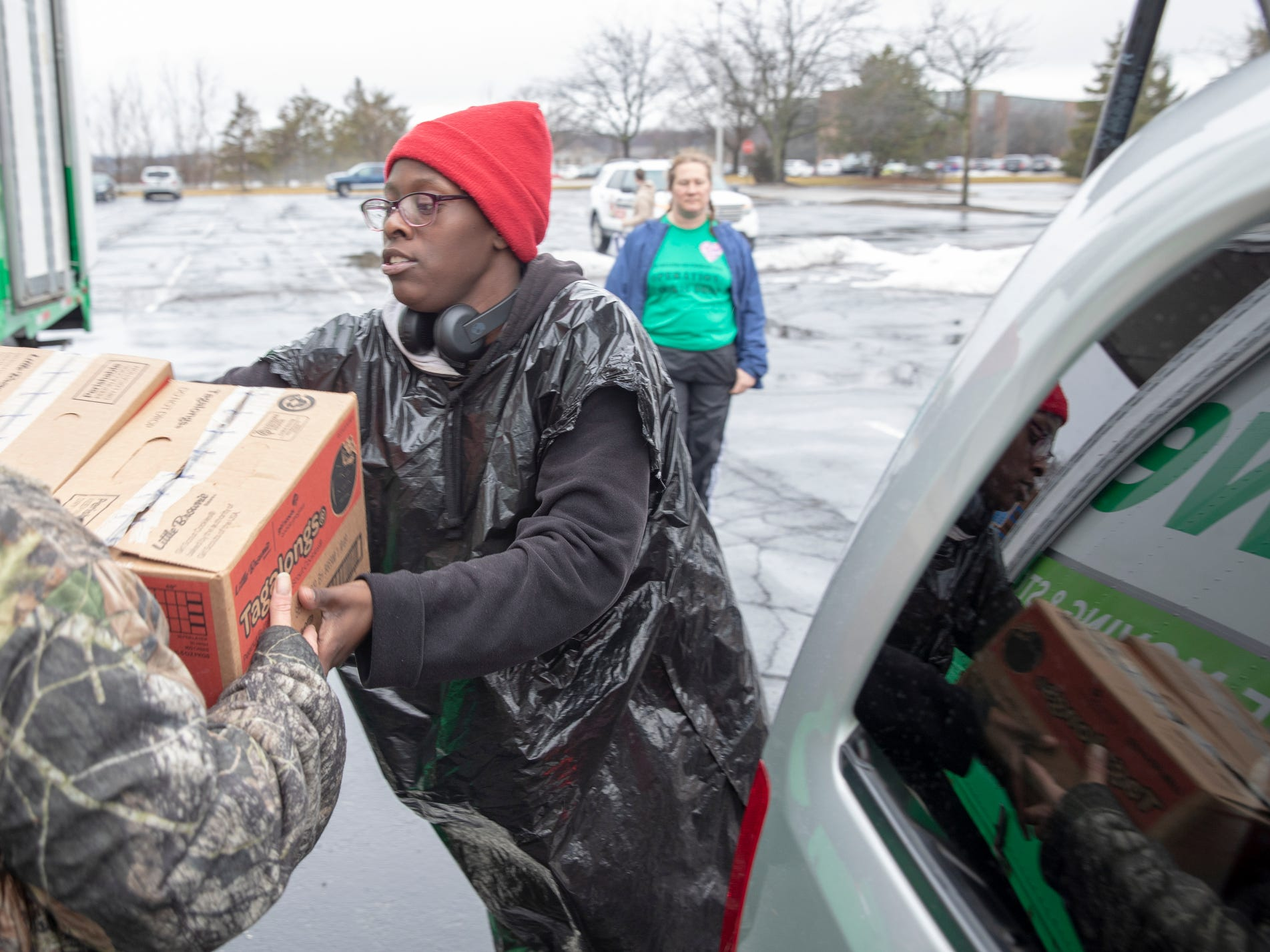 Amie'e Elliott helps load up a car during distribution for Girl Scout Cookies in Indianapolis, Wednesday, Feb. 6, 2019. The cookies will start to appear locally on the weekend, and should last into mid-March.
