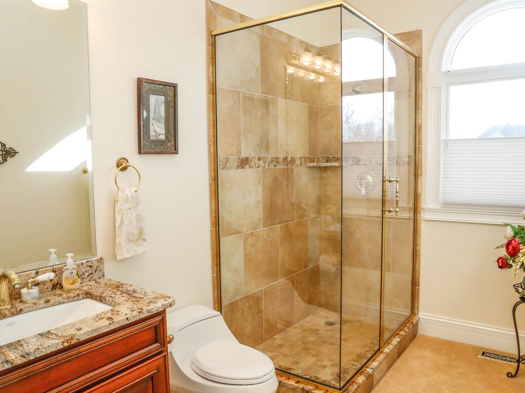 A first floor bathroom features gold accents and an italinate shower at a Greenwood home up for sale at 1216 Stone Ridge Court, Greenwood, Ind. on Wednesday, Jan. 30, 2019. The home features 8,234 square feet, four bedrooms, two master suits, a 10 car garage, and exercise room.