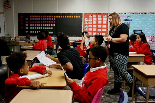 Students in Caroline Brooks' class at School 93 fill out geography worksheets, closely reading the map for information.