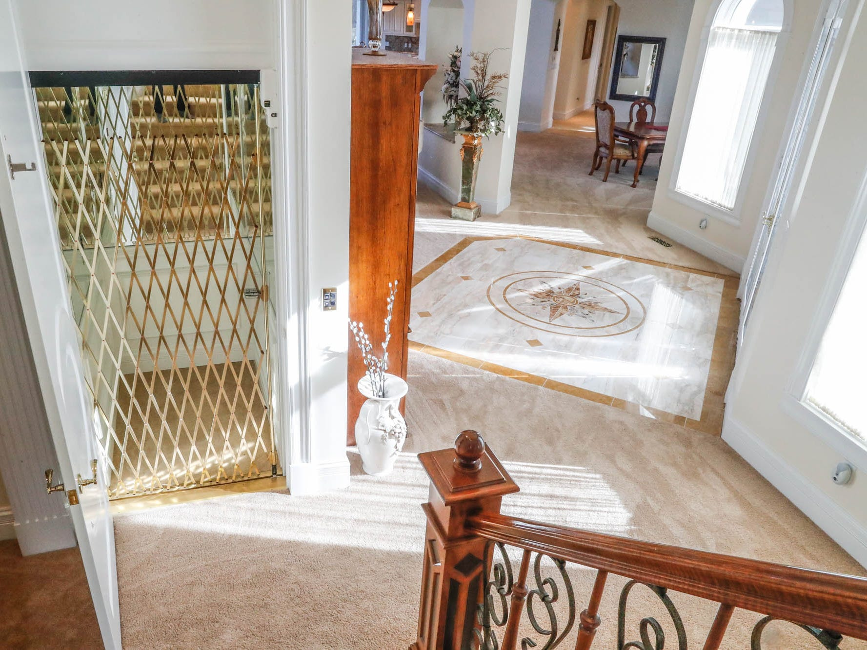 An elevator is located at the base of the grand staircase at a Greenwood home up for sale at 1216 Stone Ridge Court, Greenwood, Ind. on Wednesday, Jan. 30, 2019. The home features 8,234 square feet, four bedrooms, two master suits, a 10 car garage, and exercise room.
