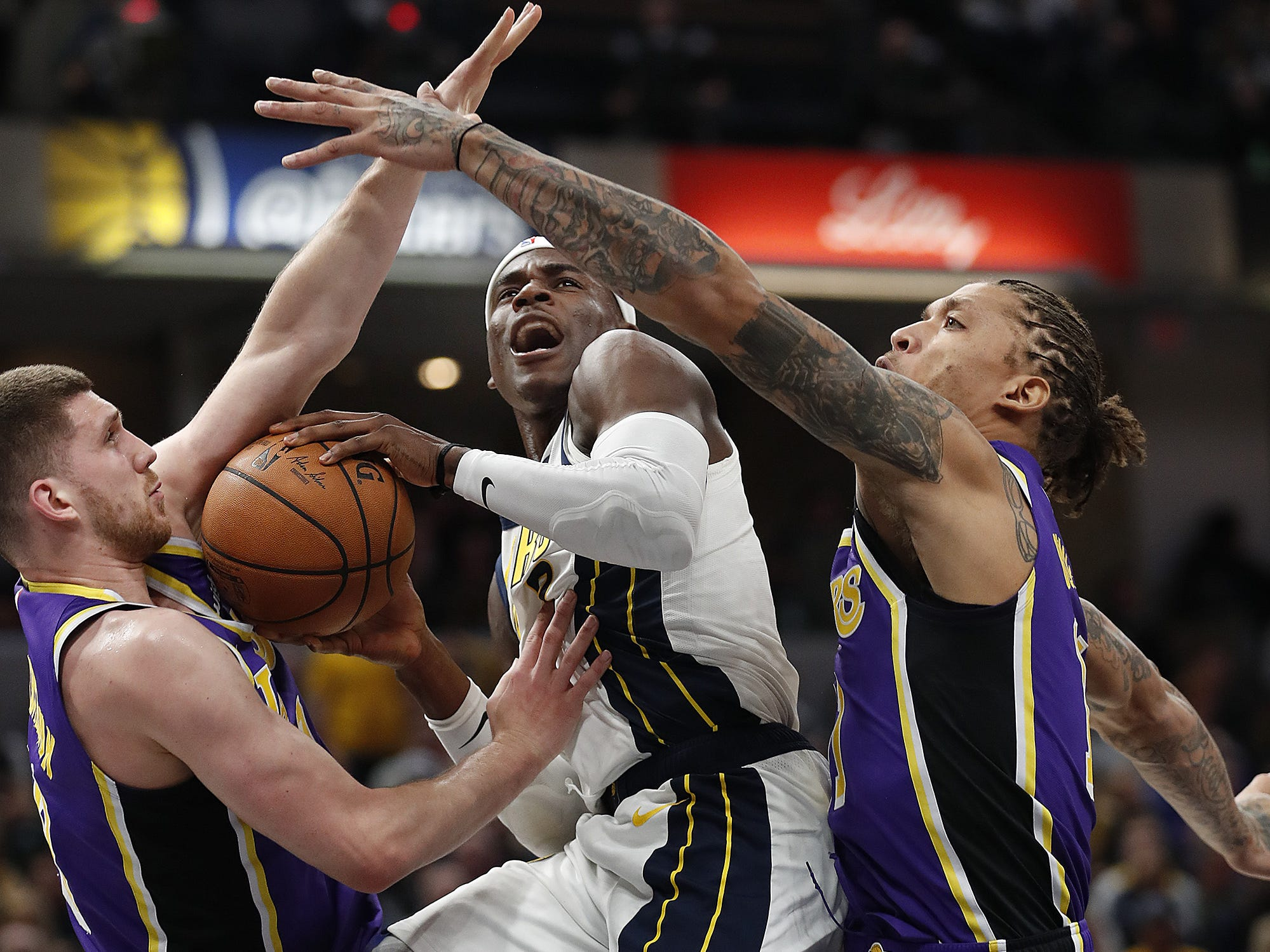 Indiana Pacers guard Aaron Holiday (3) drives between Los Angeles Lakers forward Michael Beasley (11) and Sviatoslav Mykhailiuk (10) in the second half of their game at Bankers Life Fieldhouse on Tuesday, Feb. 5, 2019.