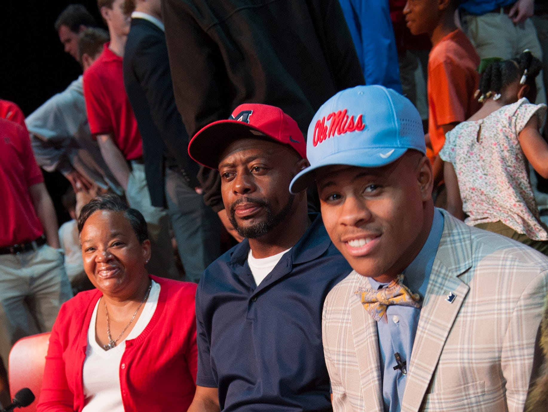 With his signed paperwork to play for Ole Miss on the table before him, a smiling Jerrion Ealy, from left, sits at the table beside his father Howard Ealy and stepmother Tricia Ealy during Sign Day activities at Jackson Prep Friday, Feb. 6, 2019.