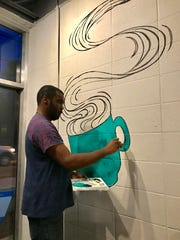 Justin Ransburg, a Jackson artist, paints an oversized coffee cup on the wall at Coffee Prose.
