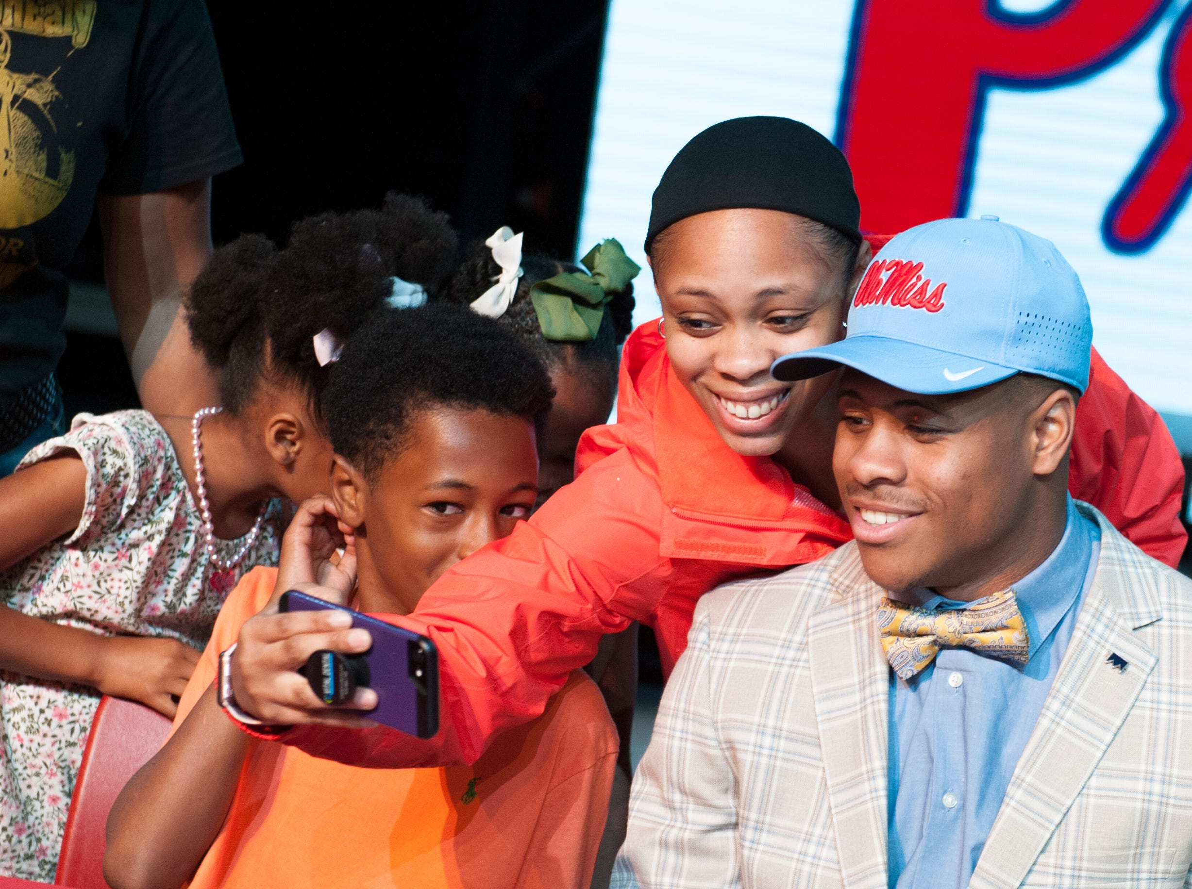 Jackson Prep's Jerrion Ealy, from right, and his sister Raven Carter smile for a selfie with Carter's son, Jeremiah Ricks, 11, as her twin daughters hide from the camera during Signing Day activities at Jackson Prep Friday, Feb. 6, 2019.