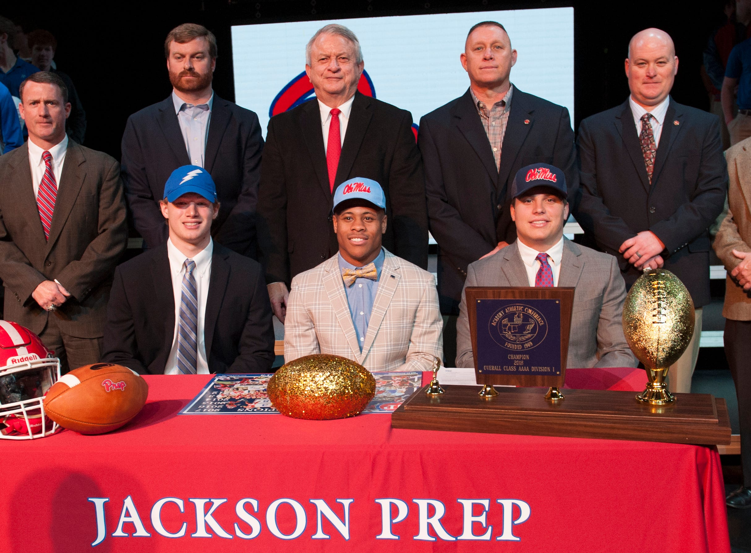 Jackson Prep's Peyton Greenwood, from left, signed with the United States Air Force Academy, and Jarrion Ealy and Adam Norsworth signed with Ole Miss during Signing Day at Prep Feb. 6, 2019. Behind them is the Jackson Prep coaching staff.